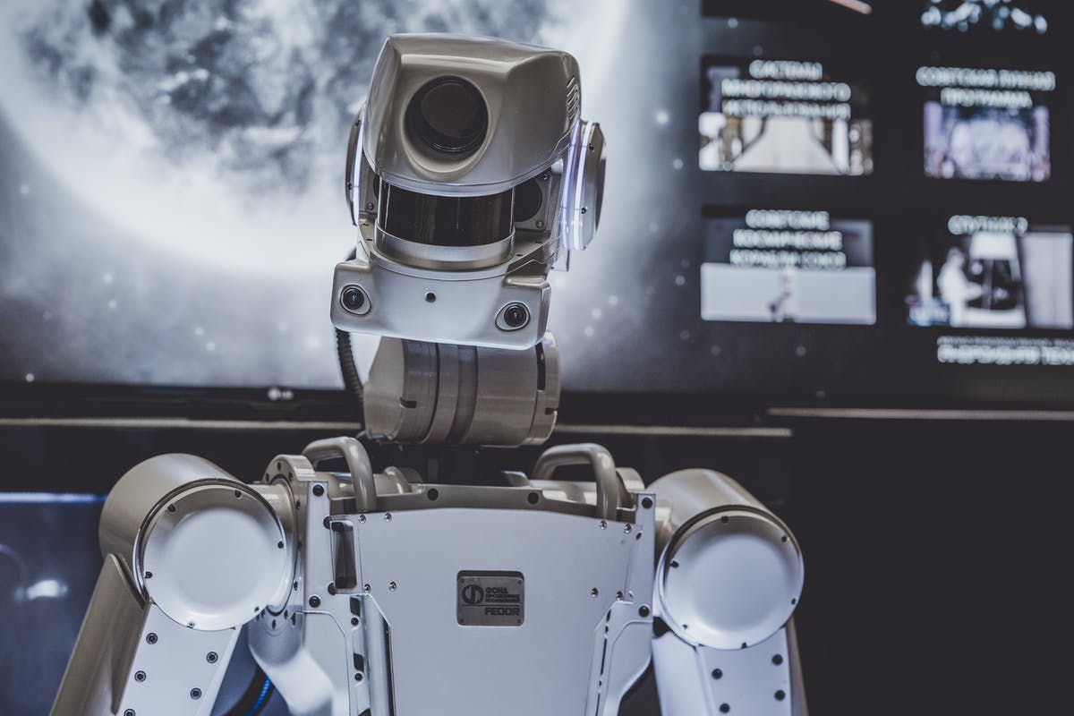 Futuristic looking robot on the bridge of a spaceship with a moon in the background on a monitor