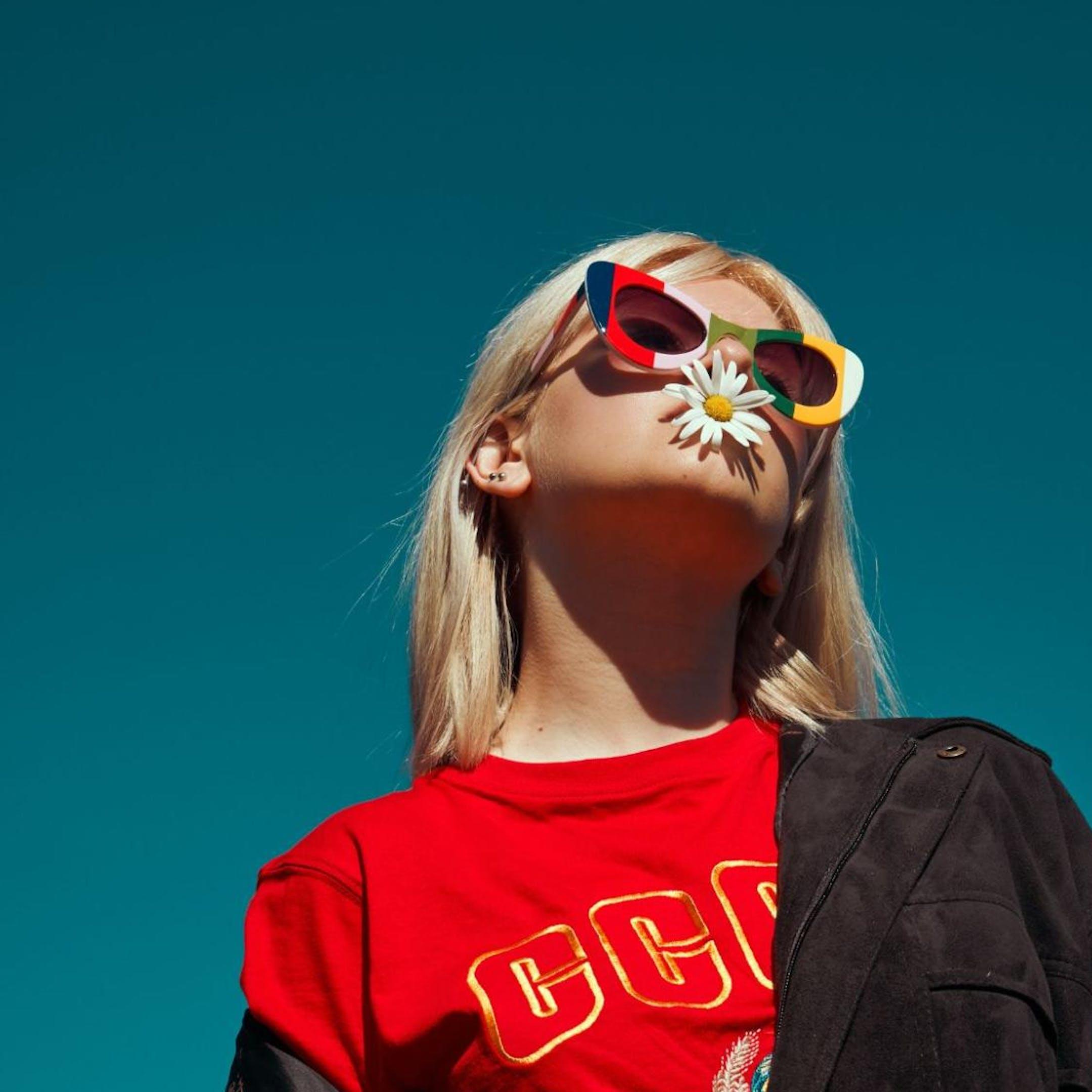 Une fille avec des lunettes et une fleur
