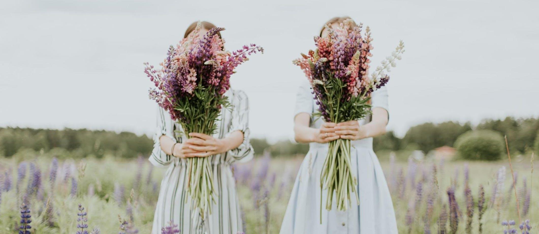 deux jeunes femmes tenant des bouquets de fleurs