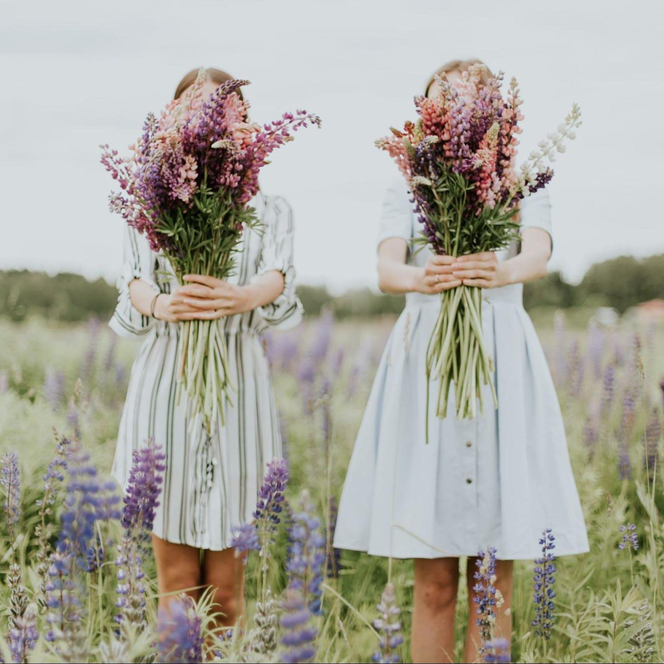 deux filles avec des bouquets de fleurs