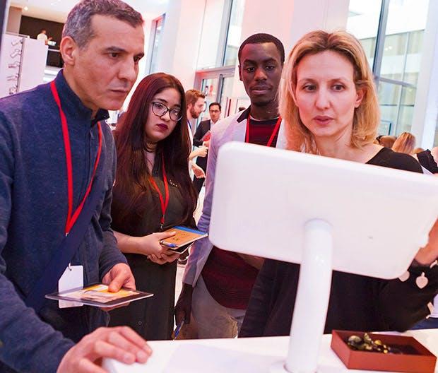 Photo d'une formation numérique en bureau de poste : quatre personnes face à un écran d'ordinateur.
