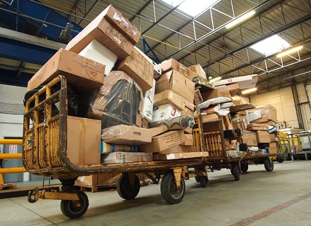Dans un entrepôt, deux chariots remplis de colis de toutes tailles.