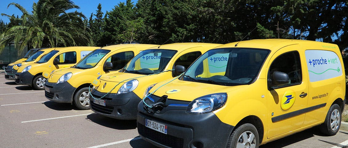 Cinq Kangoo Ze de La Poste en charge sur un parking