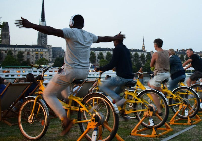 Photo de personnes qui pédalent sur des vélos jaunes face à l'écran (hors champ) d'un cinéma en plein air.