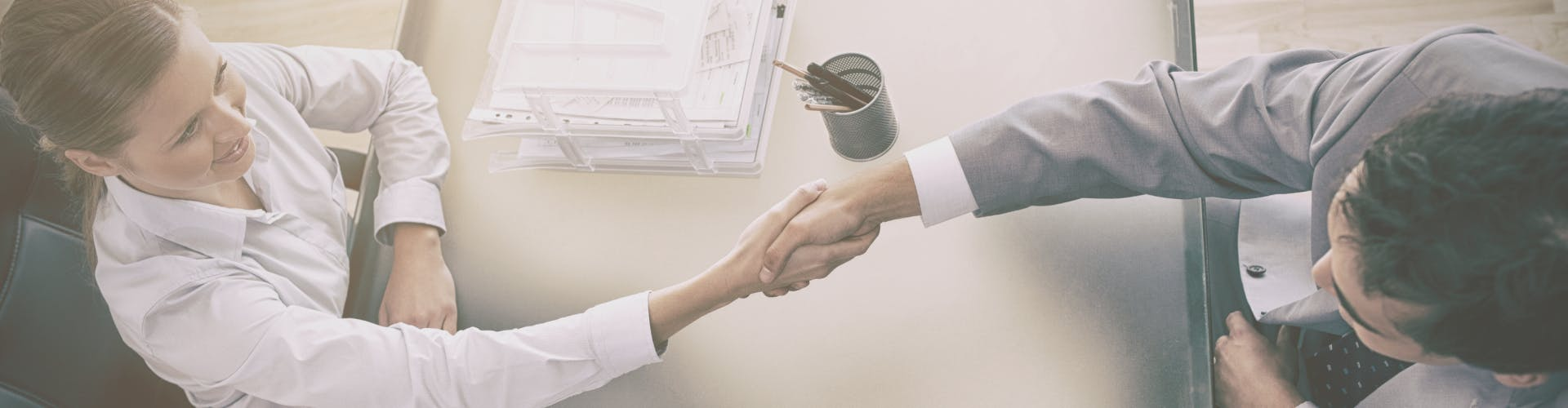 Graphics showing a handshake between the client and the company