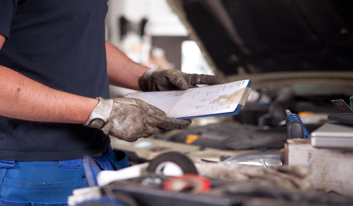 mechanic looking over clipboard