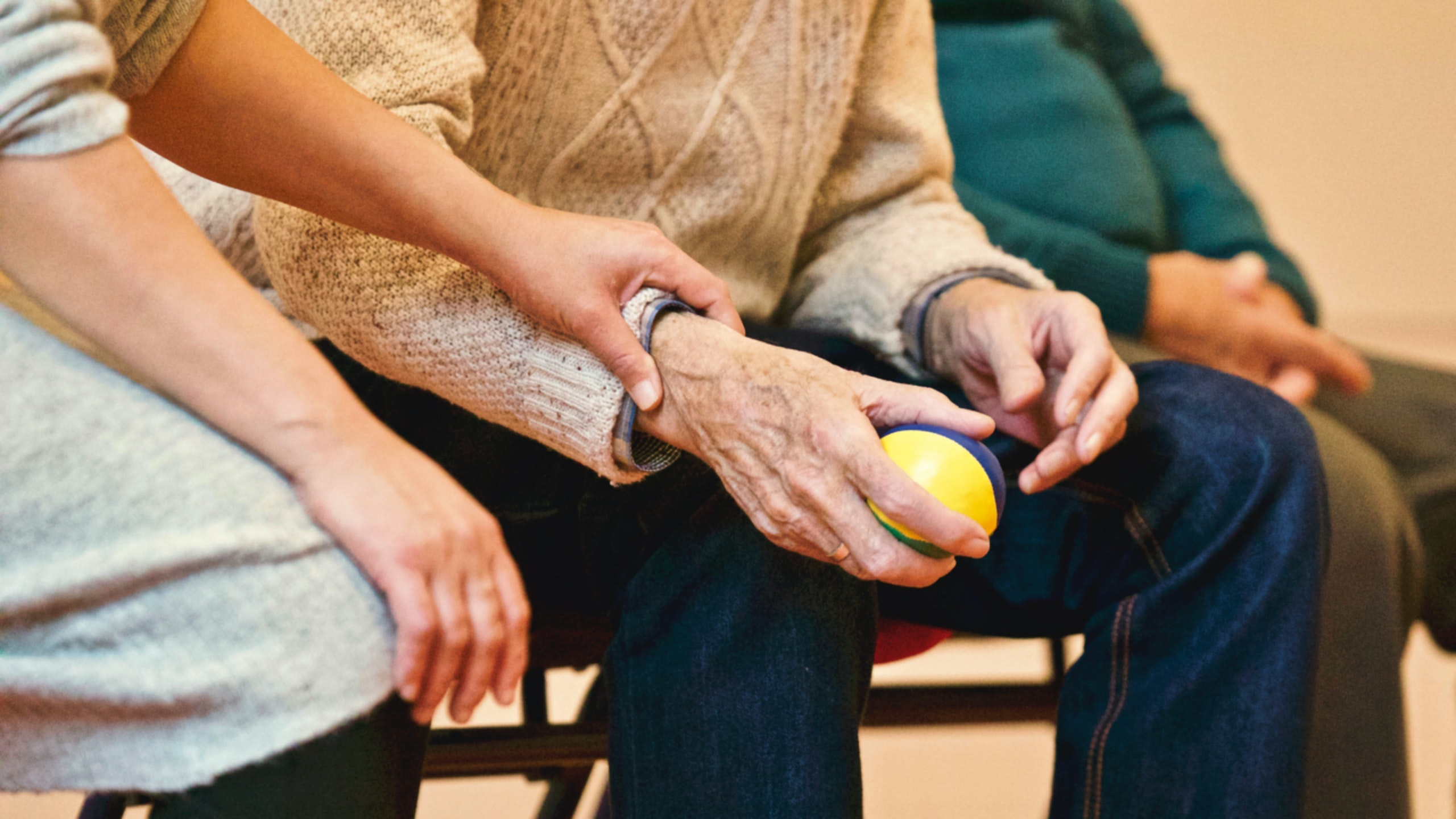 A young female hand holding the wrist of an elderly man as if checking his pulse while the elderly man is squeezing a ball.