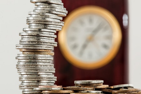 """A stack of coins in the foreground with an out-of-focus clock in the background representing """"time is money"""""""