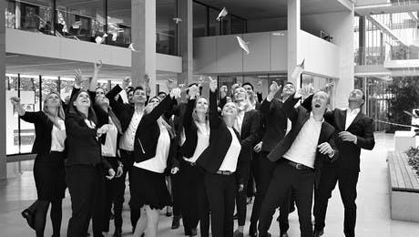 Mitarbeiter der Leitwerk Consulting München werfen Papierflieger in die Luft