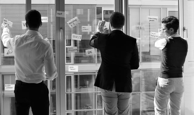 Leitwerk Berater arbeiten mit Post-its am Fenster