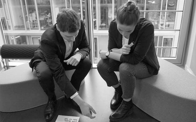 Zwei Mitarbeiter blicken auf Zettel auf dem Boden