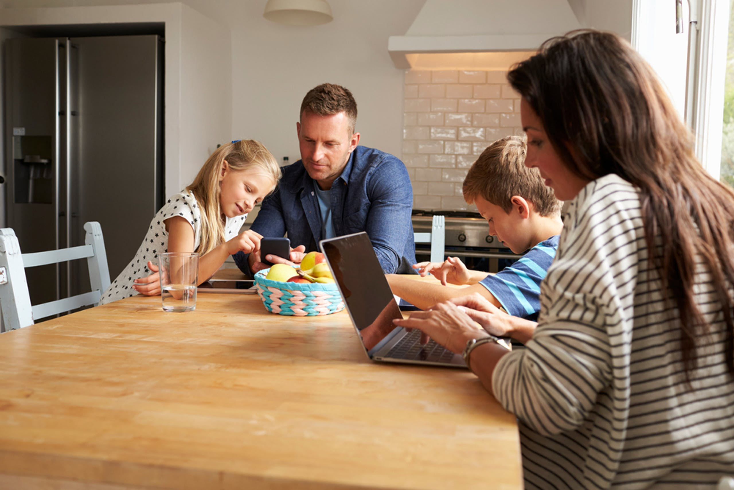 Family using devices at the kitchen table