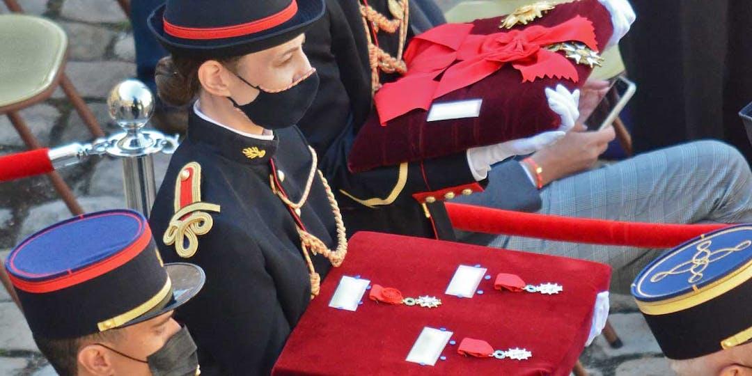 Une garde républicaine porte un coussin présentant des médailles de la Légion d'honneur avant leur remise aux récipiendaires lors d'une cérémonie aux Invalides. (LP/L'Essor)