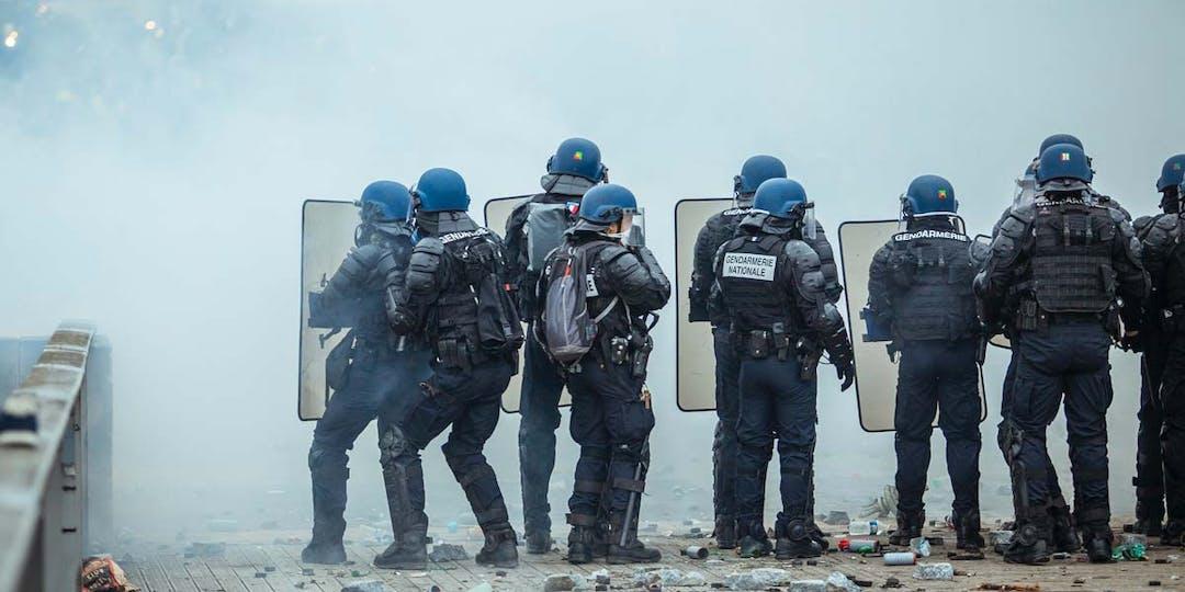 Des gendarmes mobiles lors d'une opération de maintien de l'ordre à Paris. Au sol, les restes de projectiles jetés sur eux ainsi que des grenades lacrymogènes et de désencerclement. (Photo: norbu-gyachung / unsplash)