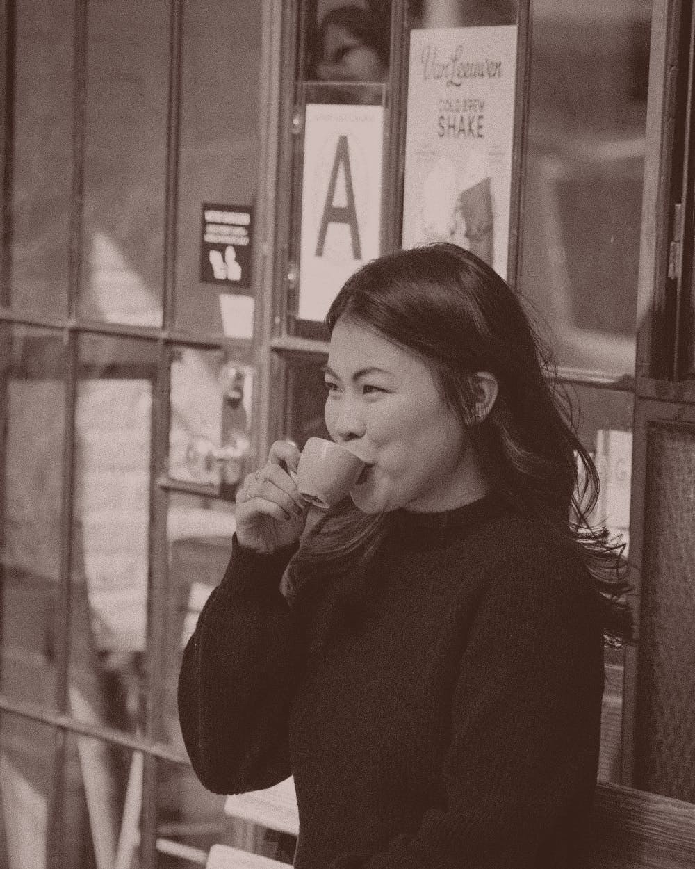 Woman drinking coffee outside.