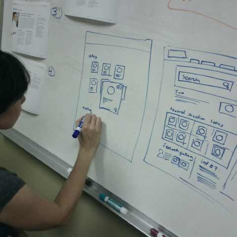 Person drawing website concepts on a whiteboard