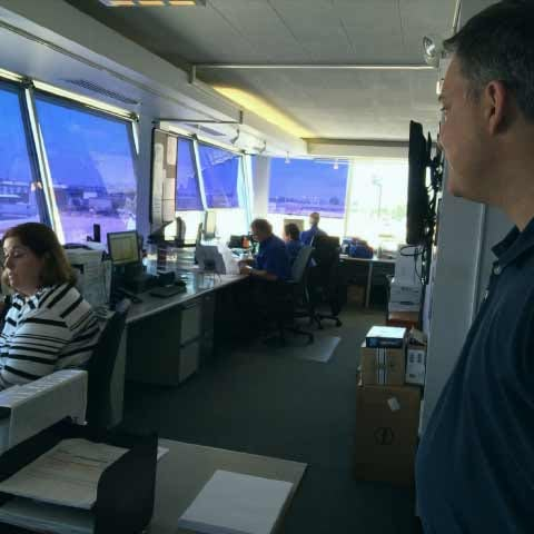 Railroad employees in a control tower supervising a train yard
