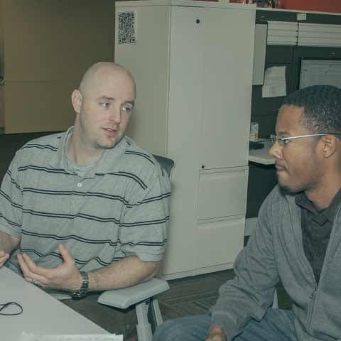 Two men seated at a desk, talking