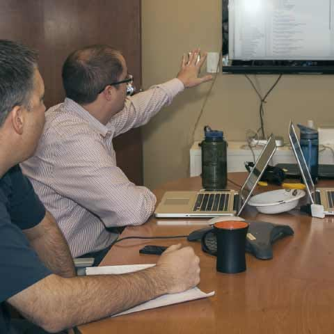 Two men seated in a conference room and looking at a large screen