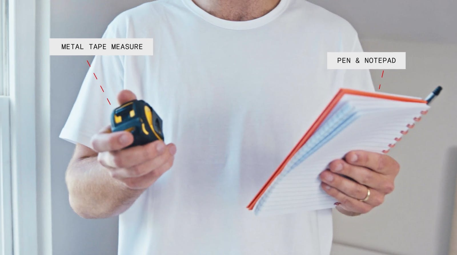 Man holding metal tape measure and pen & notepad