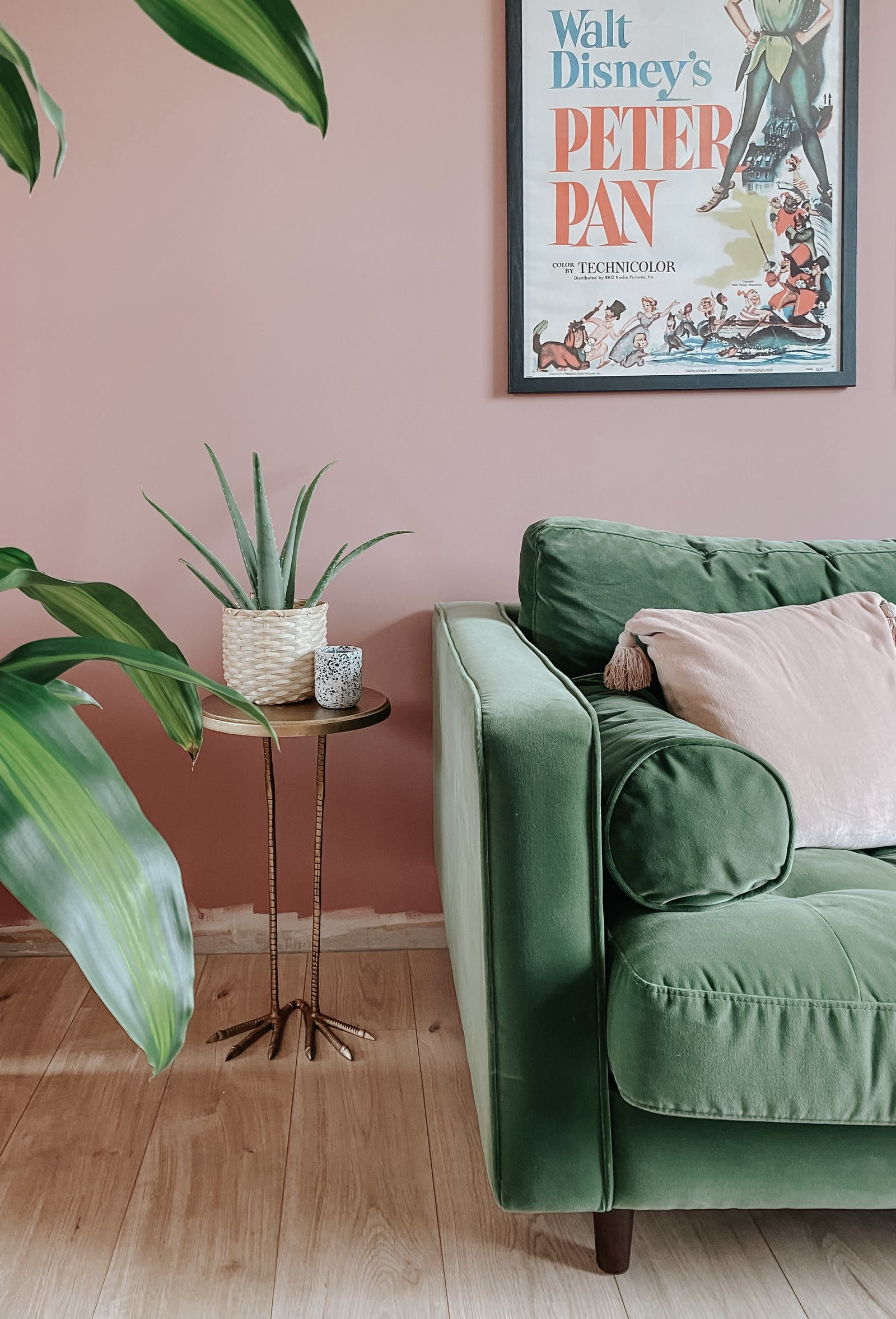 Green velvet sofa next to various plants