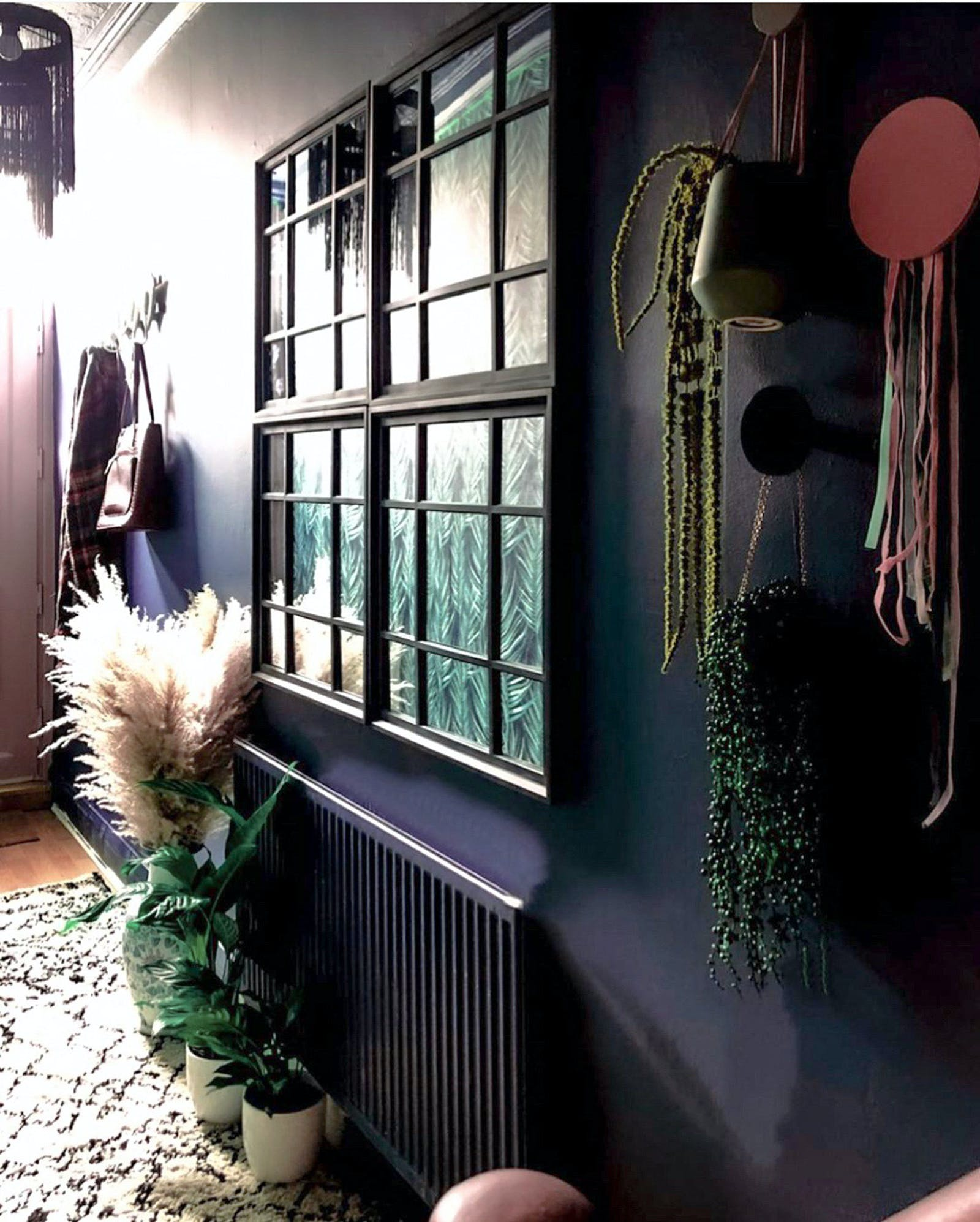 Hallway painted in black with a lot of greenery