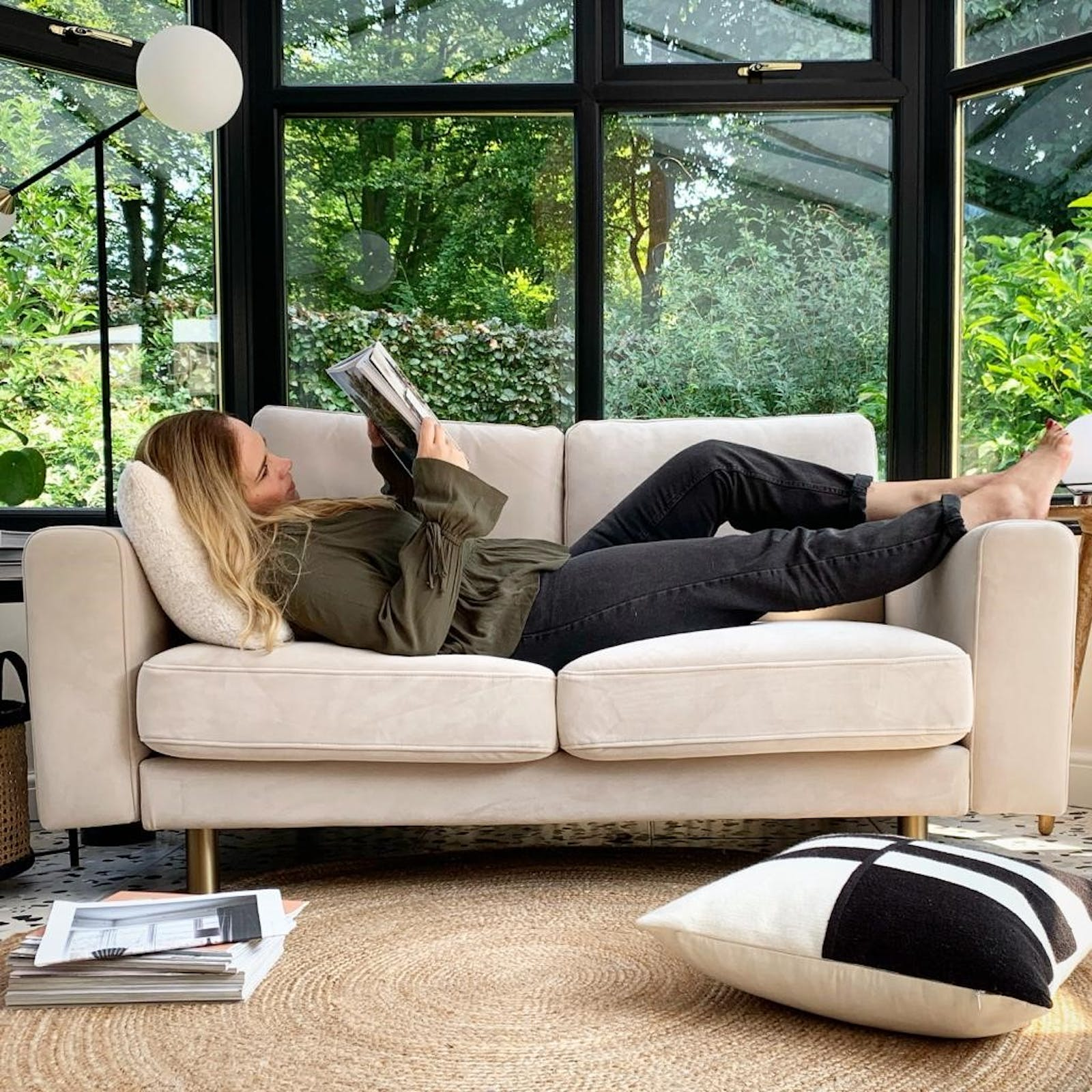Woman reading a magazine whilst lying on a sofa