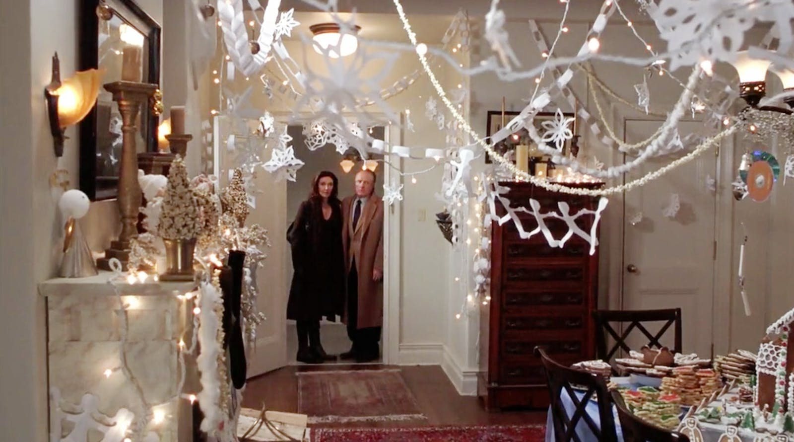 Man and woman looking into a room decorated in Christmas bunting, a famous scene in movie Elf