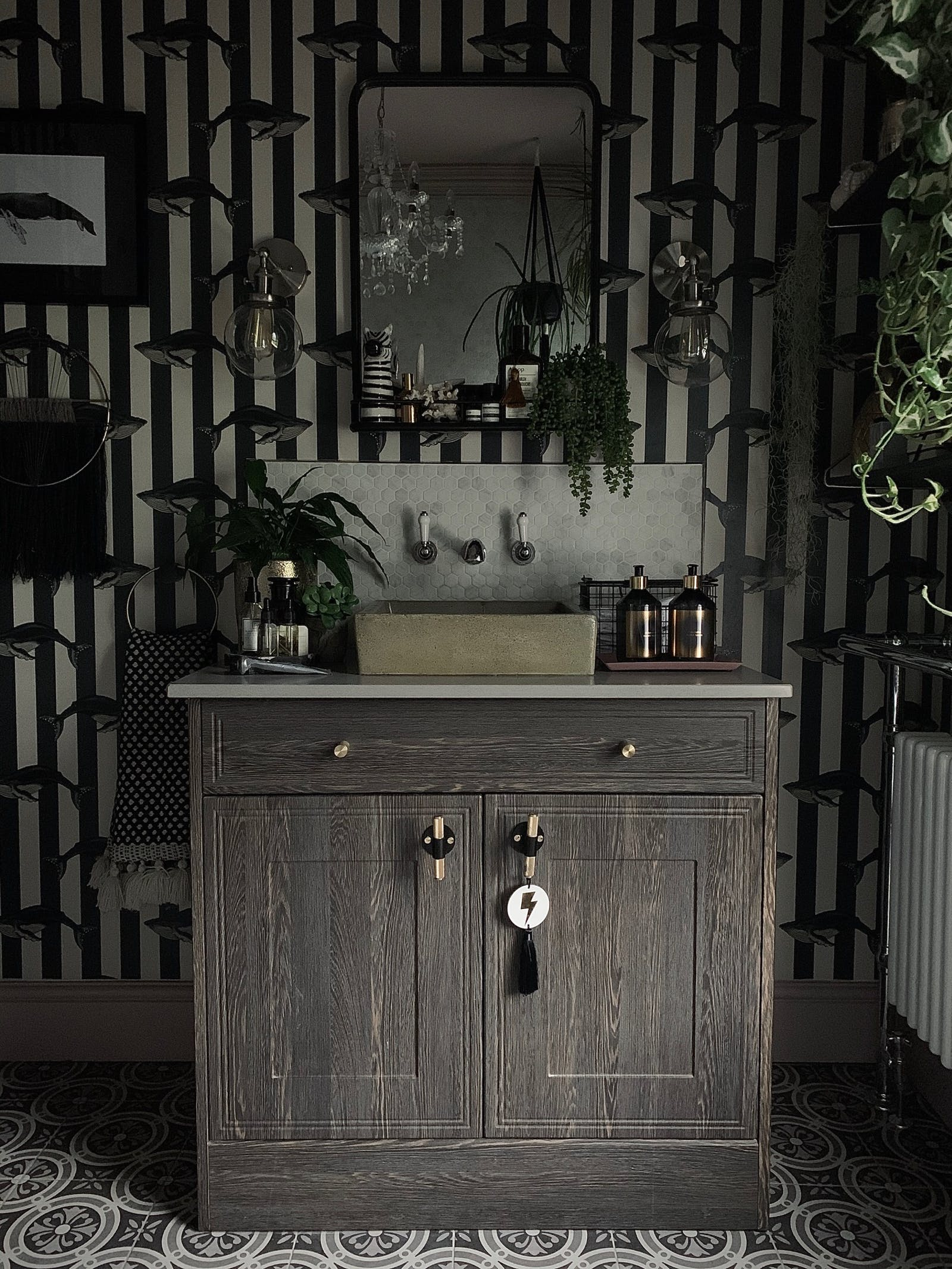 Bathroom in dark colours with lightbulbs and greenery