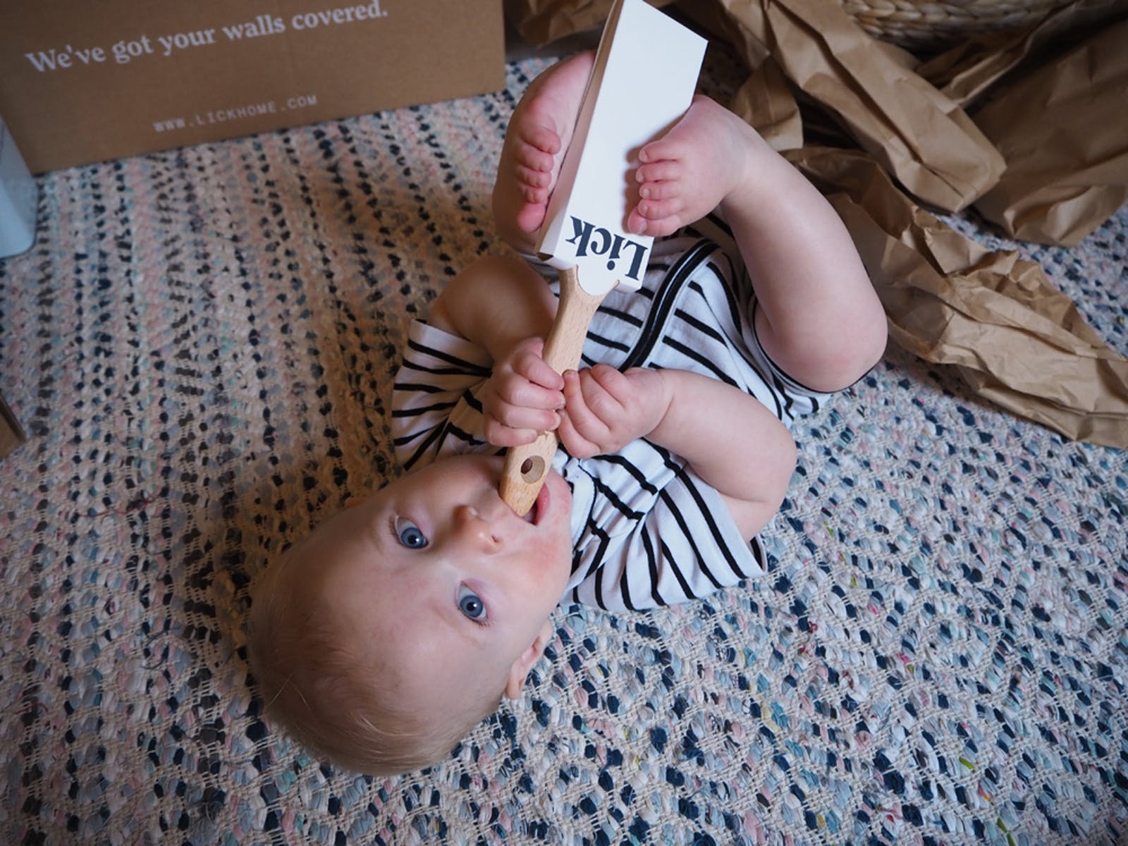 A baby chewing on an unused Lick paint brush