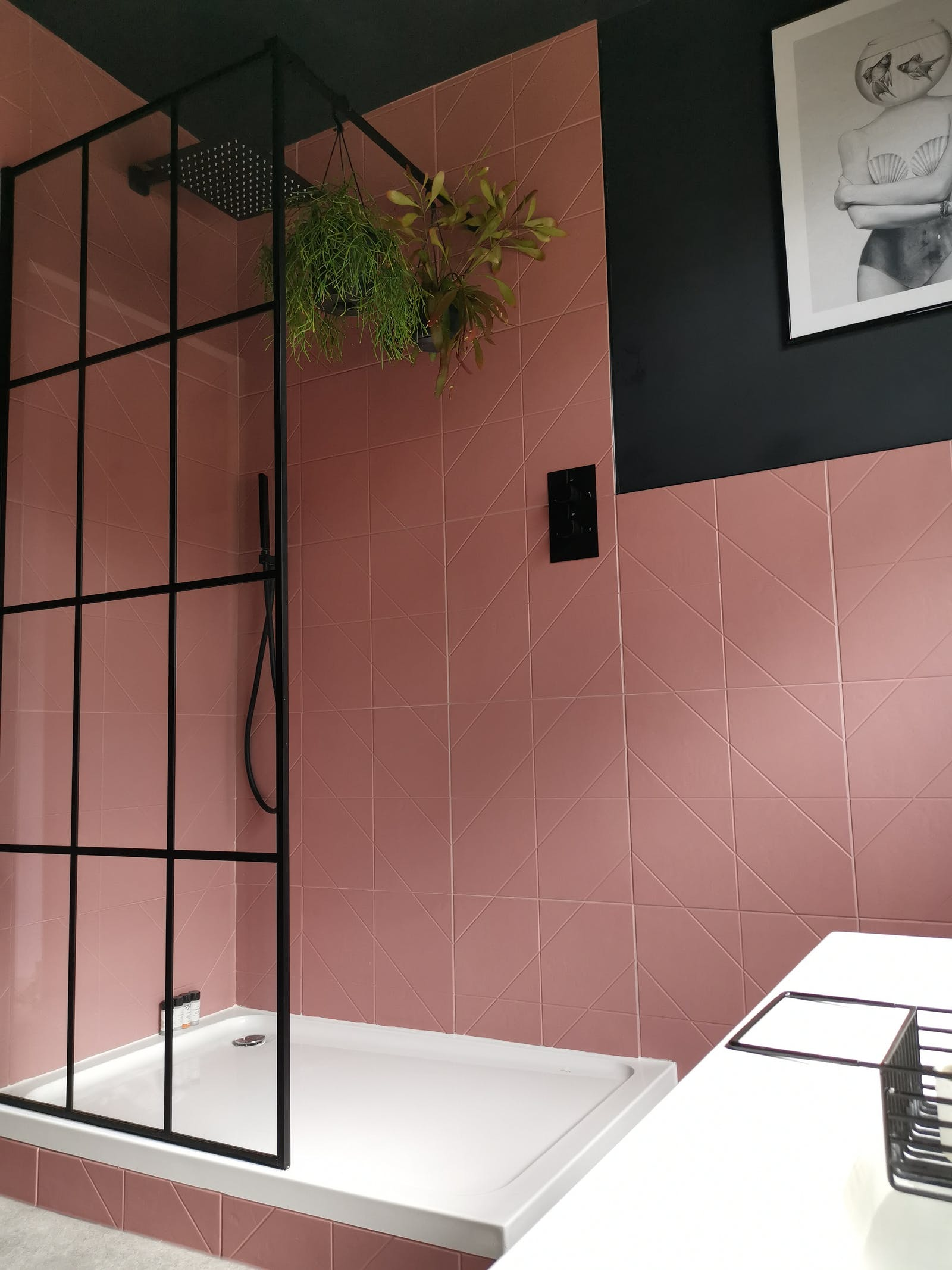 Shower area in a bathroom painted in black with pink tiles