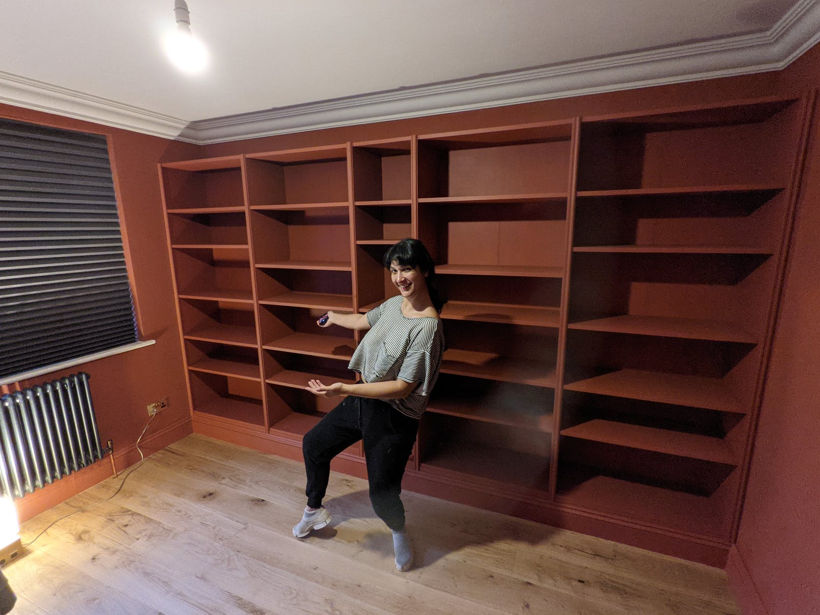 Woman standing in front of empty IKEA Billy Bookcase painted in Lick Red 01