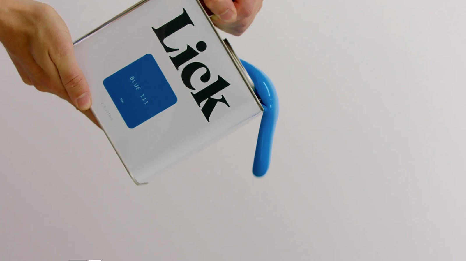 Tin of Lick Blue 111 paint being poured by hand