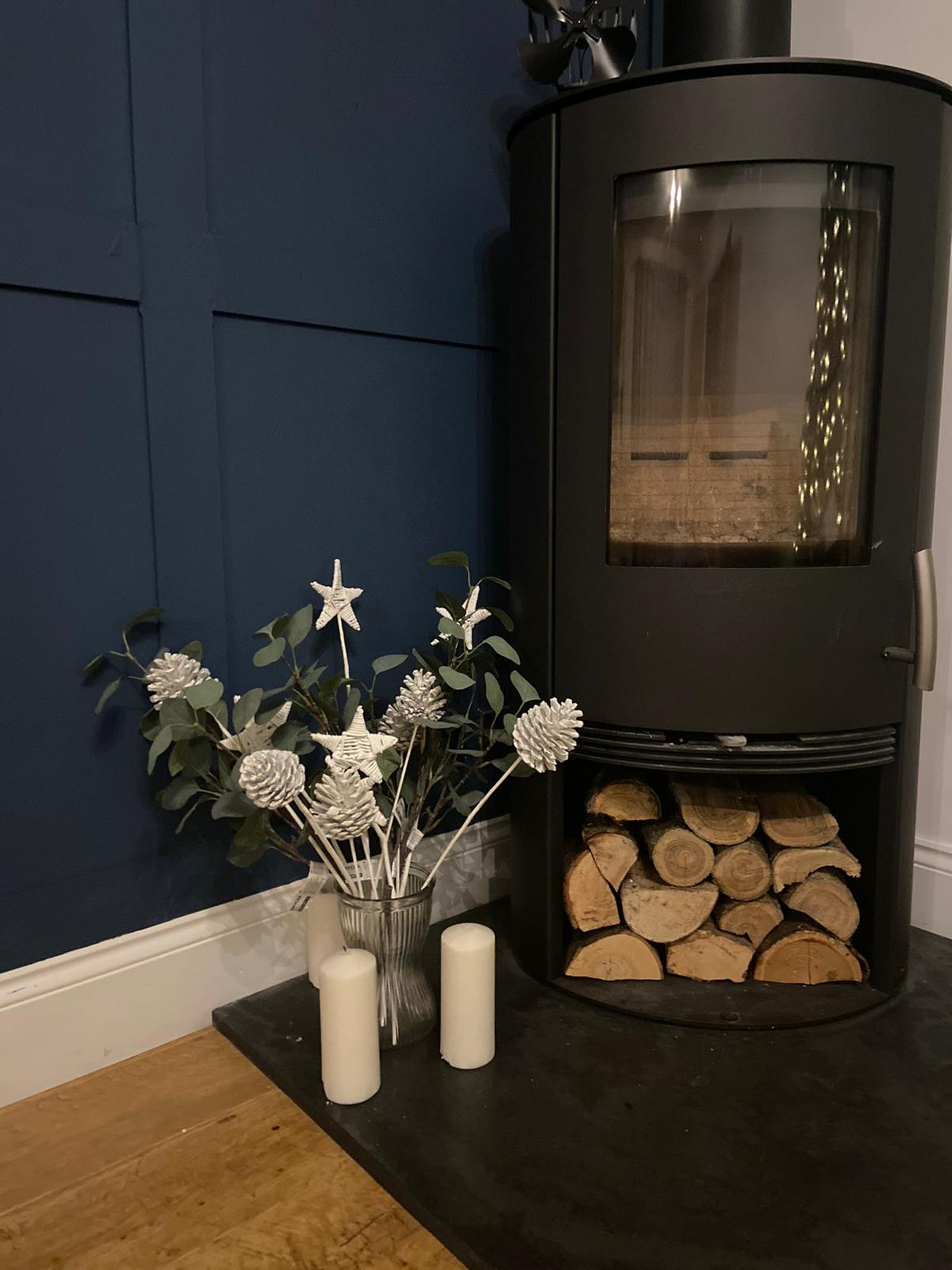 Log fireplace in living room with Lick Blue 06 painted wall panels and flowers in a vase on the floor