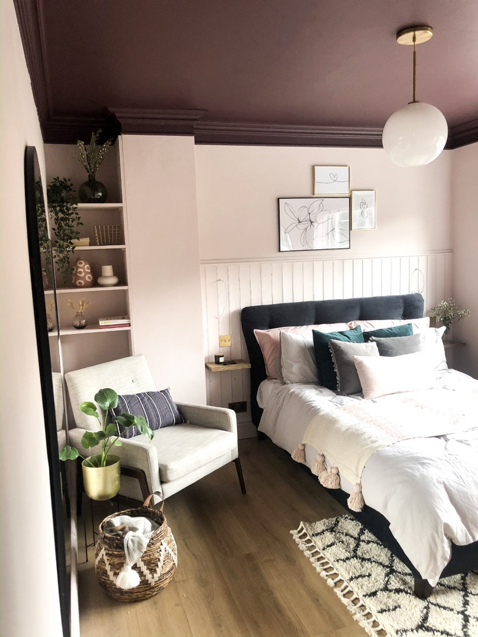 Spare bedroom painted in blush with a queen-sized bed and an armchair