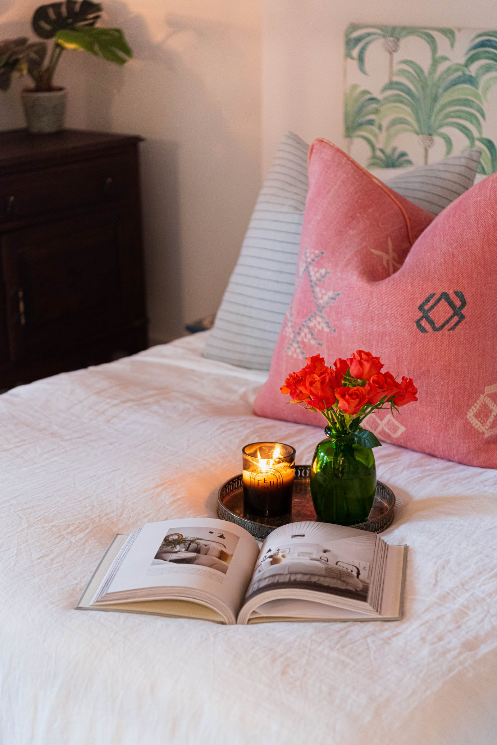 Close up image of flowers and a book on a bed that has pink and blue cushions and a palm tree pattered headboard