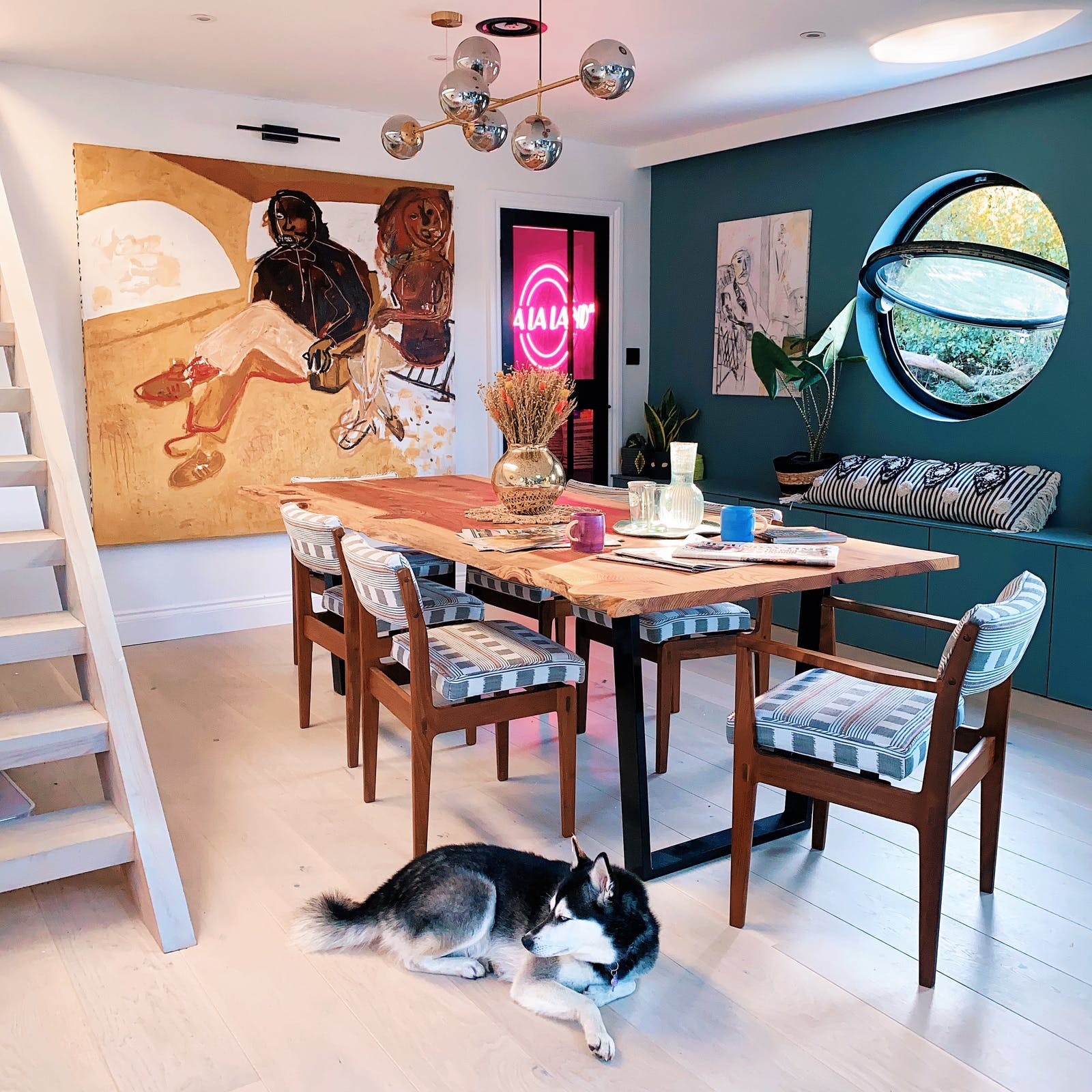 Dining table in an eclectic styled room with a husky