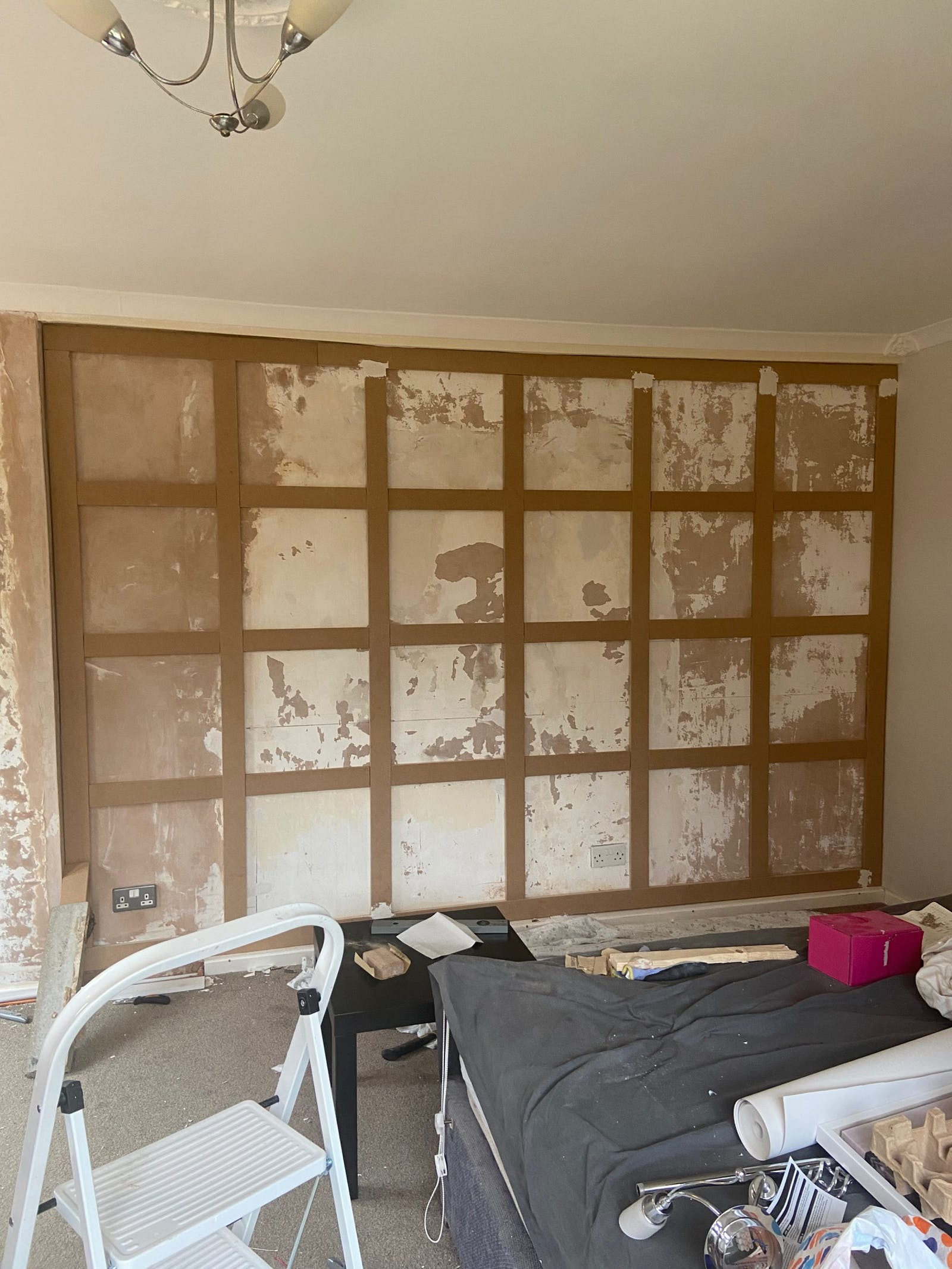 DAOB Before picture of room with peeling plaster and decorating equipment