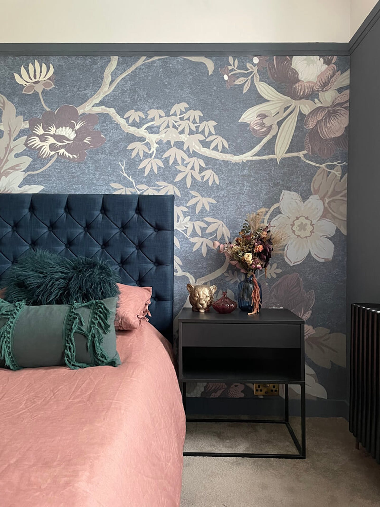Bedroom with dried flowers and floral wallpaper behind the headboard