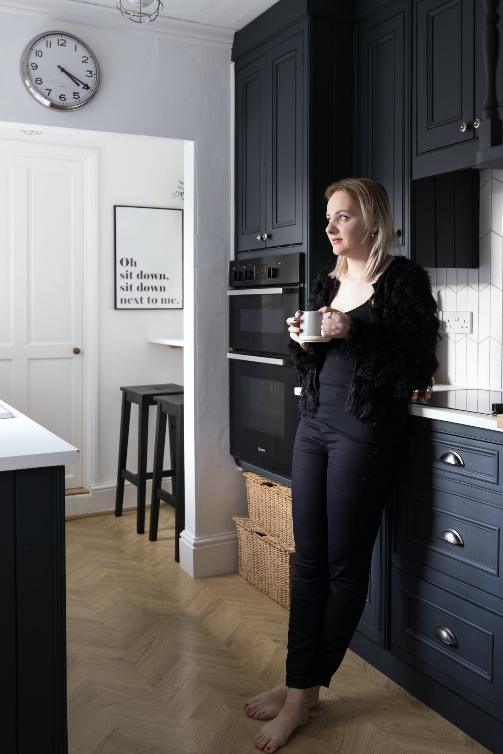 Blonde woman leaning against black kitchen cupboards painted in Lick Black 01