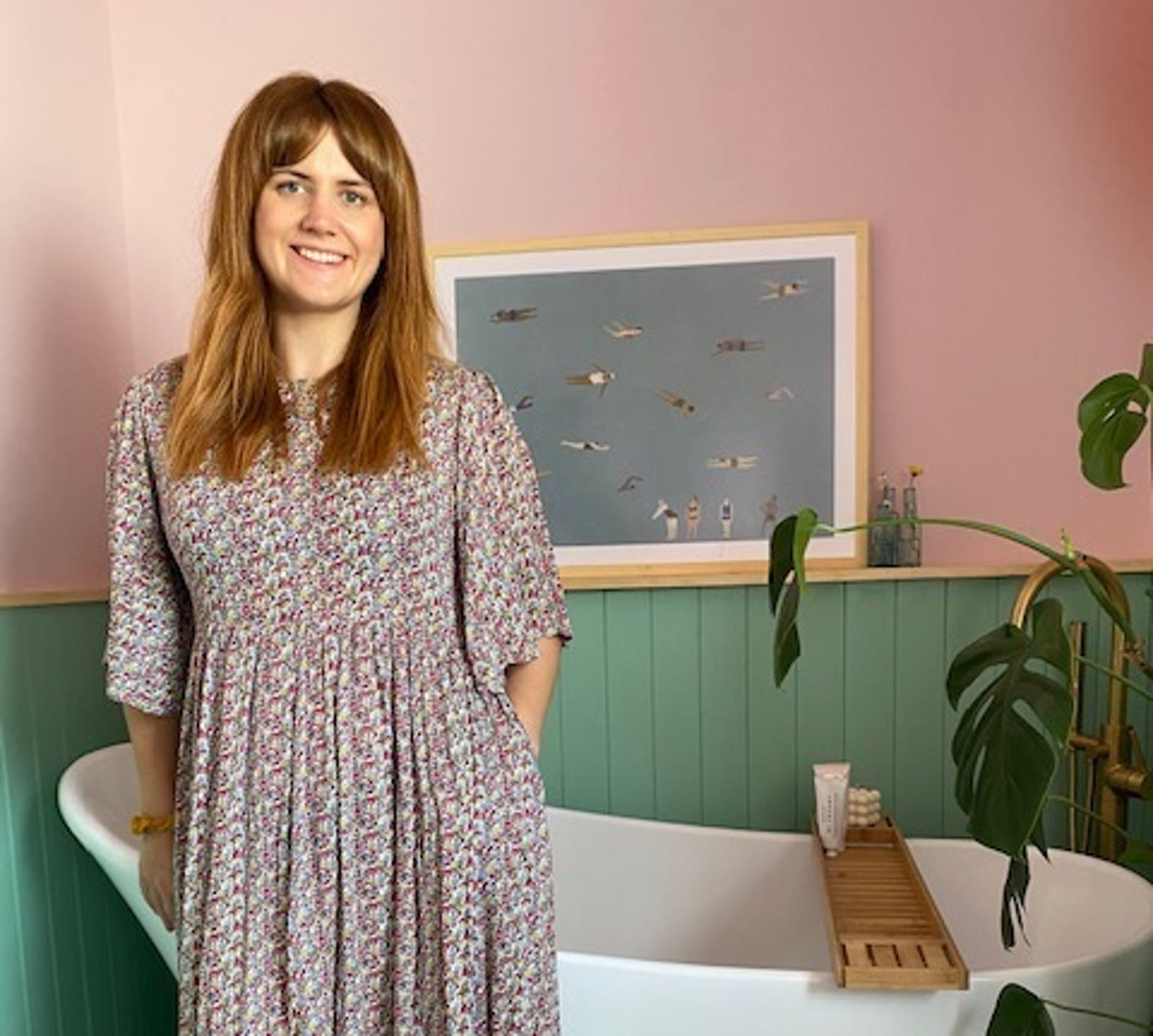 Brunette woman standing in front of bathtub in a pink and green bathroom, painted using Lick paints