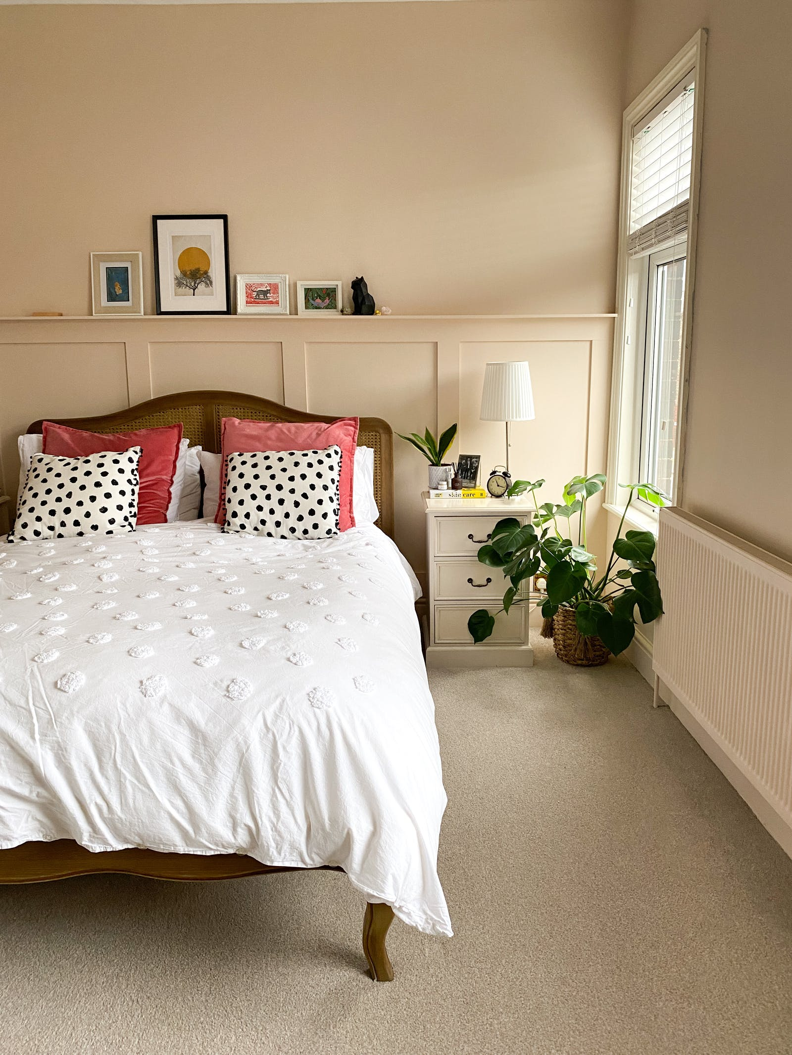 Bedroom painted in Lick Pink 02, with polkadot pillows and house plants