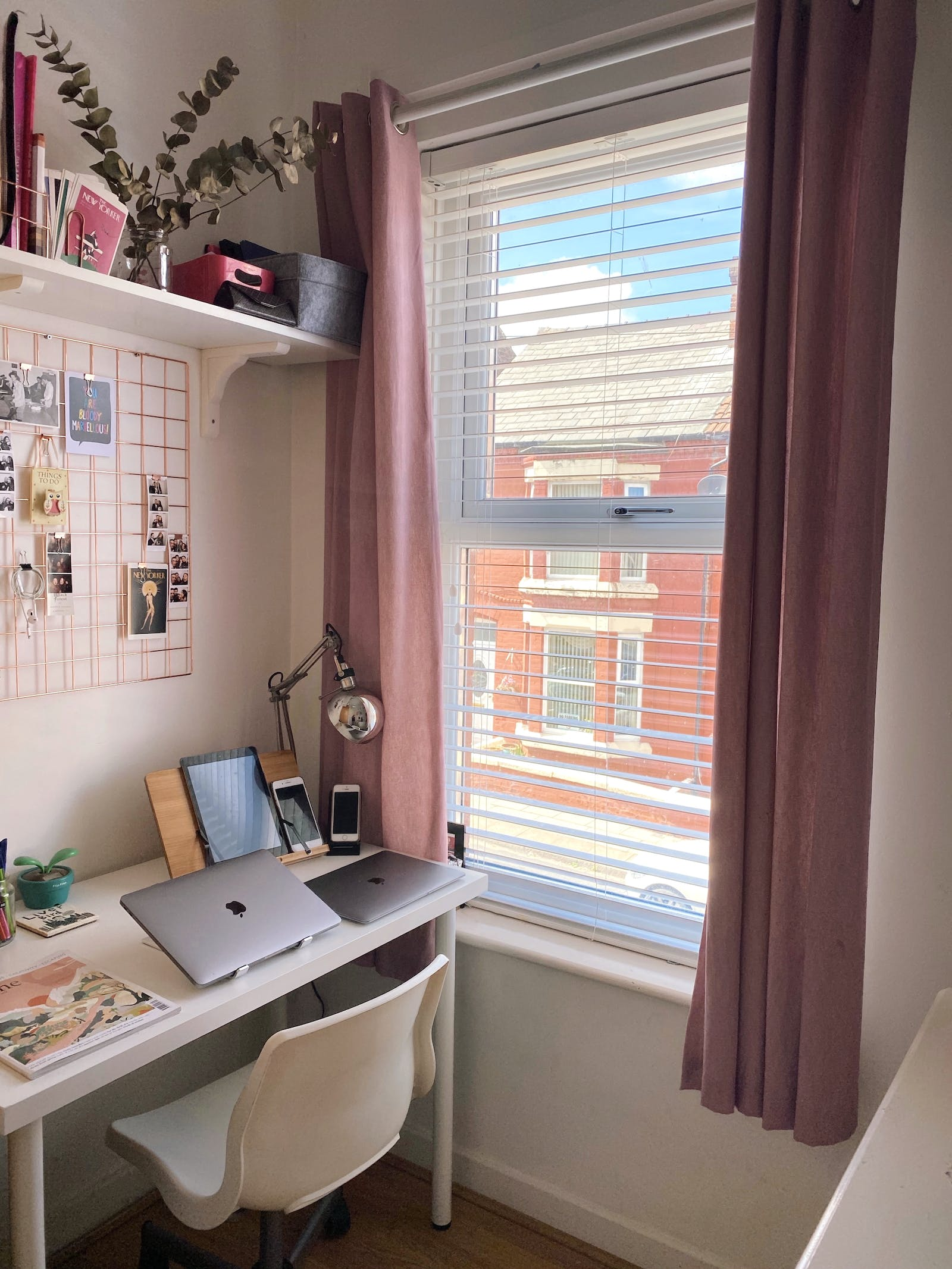 Home office corner painted in blush with dark pink curtains