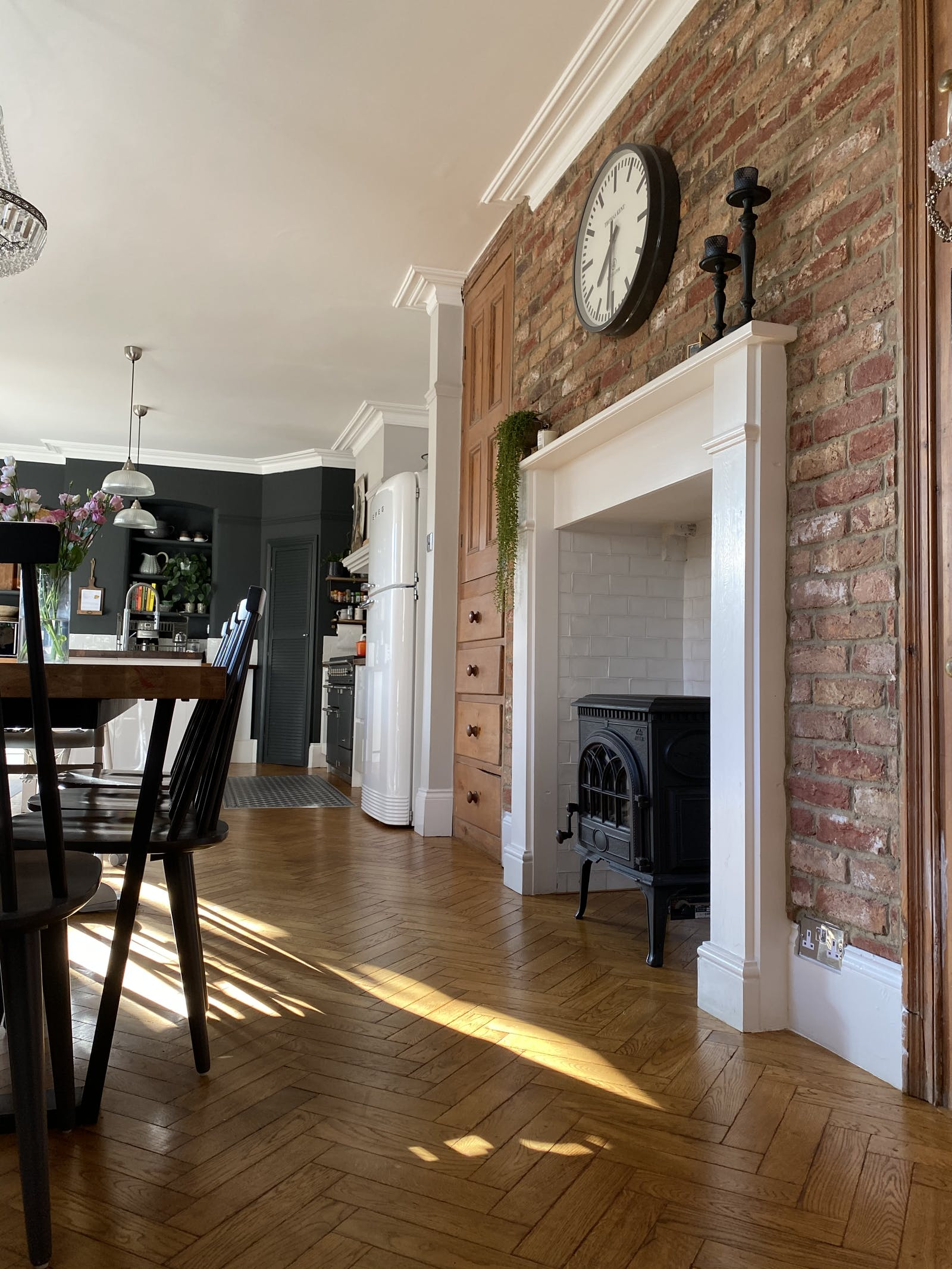 Dining room with a brick wall and a fireplace, overlooking a kitchen wall painted in black