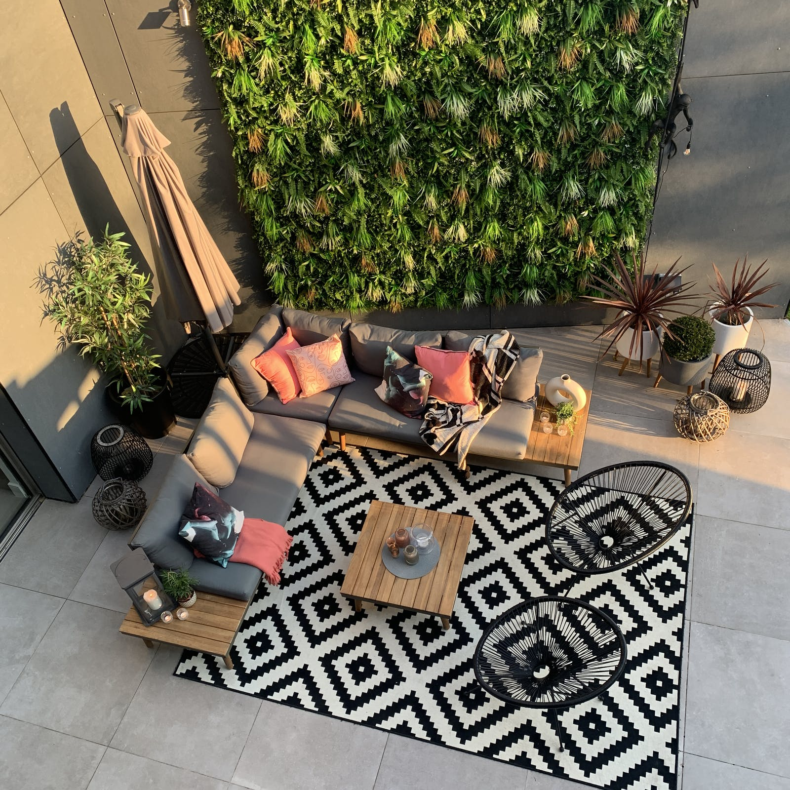 Bird's eye view of a courtyard with hanging plants covering a wall, and a monochrome geometric outdoor rug in the seating area