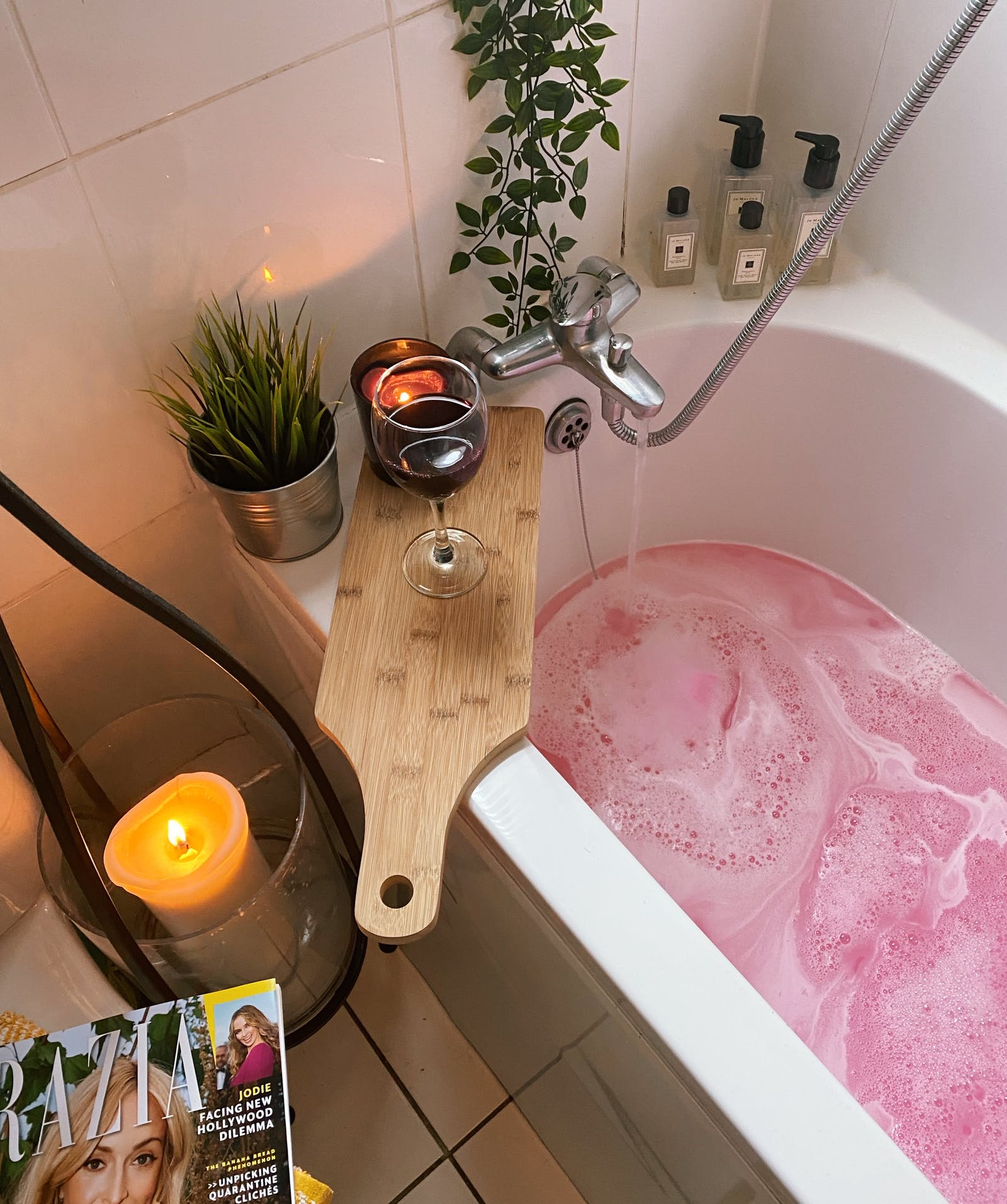 Bath with pink water and a wooden board with a glass of wine