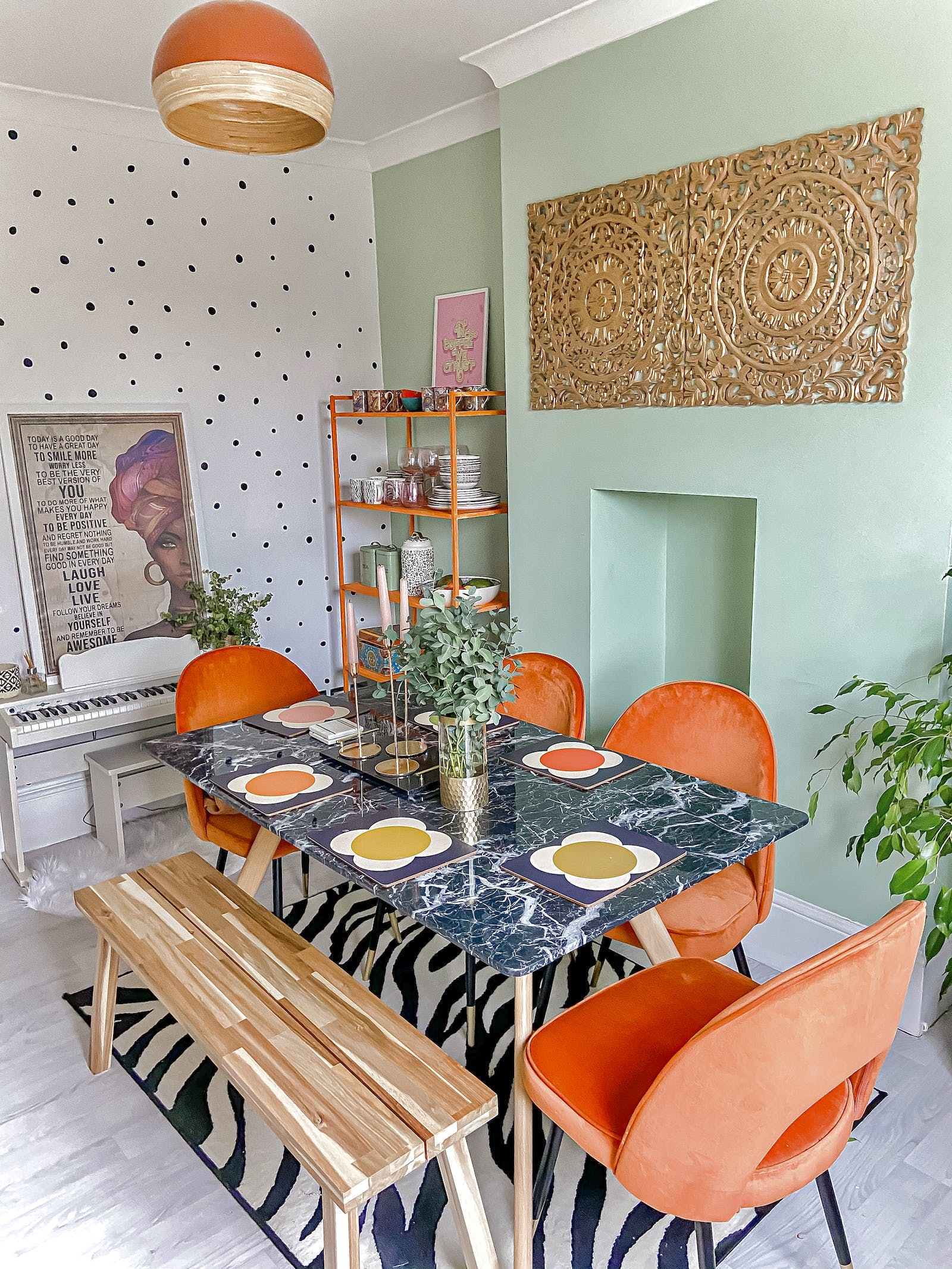 Brightly coloured dining room with polkadot wallpaper, mint green wall feature wall and orange chairs