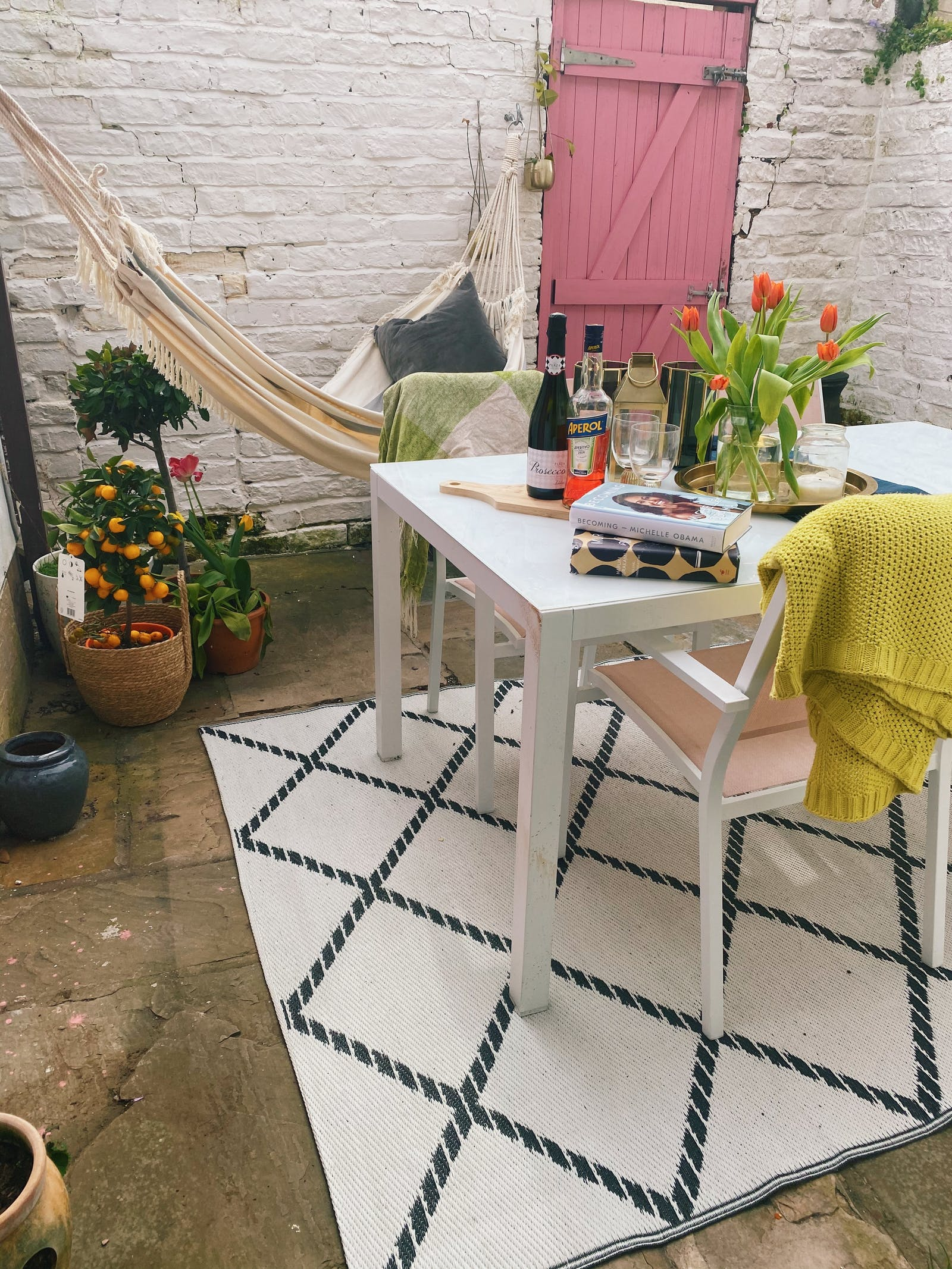 Garden with a table and a patterned rug with a door painted in pastel bubblegum pink