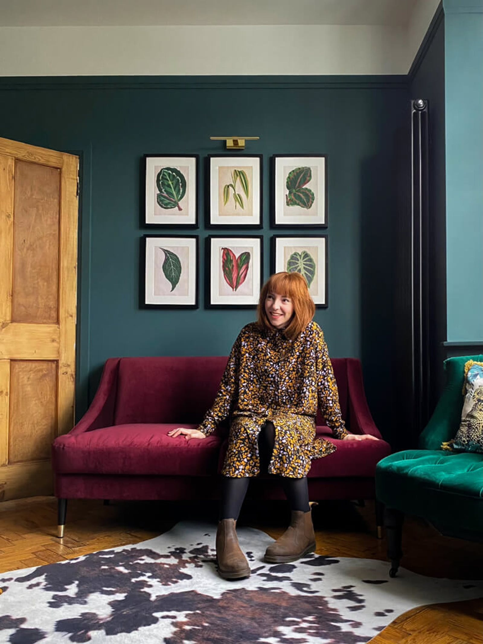 Portrait of lady in living room with velvet sofas and dark green walls