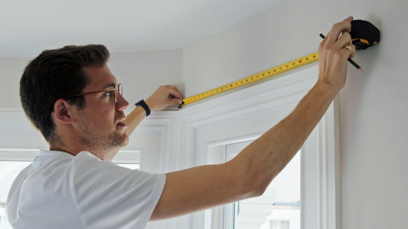 Man holding measuring tape against white wall